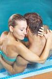 Glückliches Paar, das im Hotelpool umfasst stockfotografie