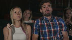 Glückliches Paar, das im Kino, das Popcorn essend sitzt und lächeln stock video footage