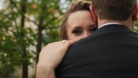 Glückliches Paar, das im Park an einem sonnigen Tag umfasst stock video