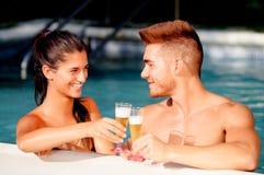 Glückliches Paar, das im Pool sich entspannt stockfotos