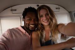 Glückliches Paar, das im Reisemobil sitzt lizenzfreies stockfoto