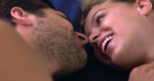 Glückliches Paar, das im sprechenden und lachenden Bett liegt stock footage