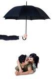 Glückliches Paar, das im Studio unter Regenschirm küsst Lizenzfreies Stockfoto