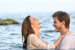 Glückliches Paar, das im Wasser auf dem Strand scherzt lizenzfreie stockfotos