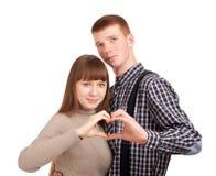 Glückliches Paar, das Inneres mit ihren Fingern zeigt Lizenzfreie Stockfotos