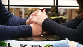 Glückliches Paar, das jede andere Hände am Café im Einkaufszentrum hält und berührt Männliche Hände streichen die weibliche Hand stock footage