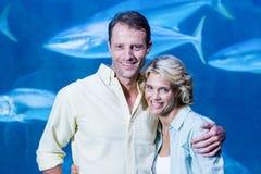 Glückliches Paar, das Kamera neben dem Aquarium betrachtet stockbild