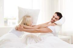 Glückliches Paar, das Kissenschlacht im Bett zu Hause hat stockbild