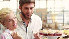 Glückliches Paar, das kleine Kuchen auf Restaurant zeigt stock video footage