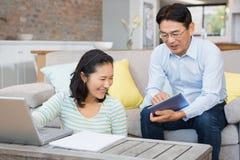 Glückliches Paar, das Laptop und Tablette verwendet Stockbild