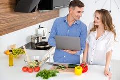 Glückliches Paar, das Laptop verwendet und vegetarische Teller vorbereitet Lizenzfreies Stockfoto