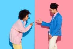 Glückliches Paar, das lustige Schatten auf Rosa und Blau gestikuliert und macht Stockfotos