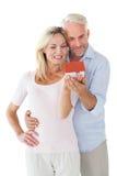 Glückliches Paar, das Miniaturmusterhaus hält Stockfotografie