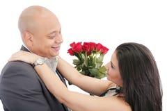 Glückliches Paar, das mit einem Blumenstrauß von roten Rosen in der Mitte umarmt. Lizenzfreies Stockbild