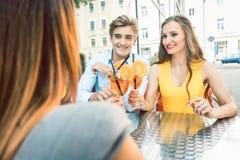 Glückliches Paar, das mit ihrer gegenseitigen Freundin an einem modischen Restaurant röstet Stockbild