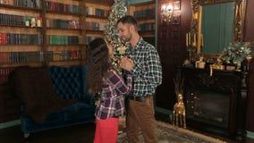 Glückliches Paar, das nahe bei einem Weihnachtsbaum steht stock video footage