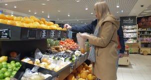Glückliches Paar, das Orangen im Supermarkt wählt stock video