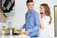 Glückliches Paar, das Pfannkuchen brät und auf Küche flirtet Stockbilder