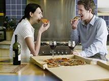 Glückliches Paar, das Pizza in der Küche isst Lizenzfreie Stockfotos