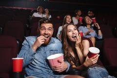 Glückliches Paar, das Popcorn und das Lachen isst stockfotografie