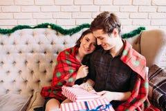 Glückliches Paar, das Rest nahe Weihnachtsgeschenken hat Stockbilder