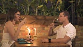 Glückliches Paar, das Rotwein am romantischen Abendessen mit Kerzen im Restaurant trinkt Mann und Frau, die Rotwein von trinken stock video footage