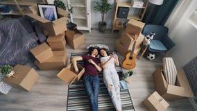 Glückliches Paar, das Sachen vom Kasten liegt auf dem Teppich sich entspannt während der Verlegung nimmt stock footage