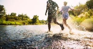 Glückliches Paar, das in seichtes Wasser läuft stockbild
