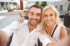Glückliches Paar, das selfie an der Restaurantterrasse nimmt Stockbild