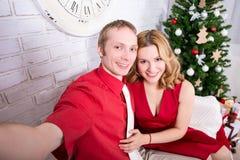 Glückliches Paar, das selfie Foto vor Weihnachtsbaum macht Lizenzfreies Stockfoto