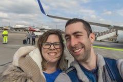 Glückliches Paar, das selfie mit Smartphone oder Kamera im Flughafen nimmt Lizenzfreie Stockbilder