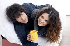 Glückliches Paar, das sich in aufpassendem Fernsehen des Schlafzimmers hinlegt Stockbild