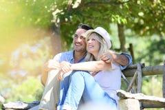 Glückliches Paar, das sich draußen auf der Bank entspannt Stockbilder