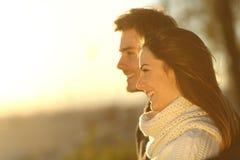 Glückliches Paar, das Sonnenuntergang im Winter betrachtet stockfotos