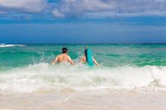 Glückliches Paar, das Spaß auf dem Strand von einer Tropeninsel hat Summe Stockfotos