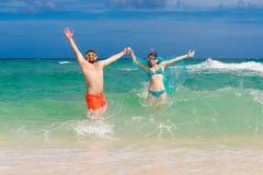 Glückliches Paar, das Spaß auf dem Strand von einer Tropeninsel hat Summe Lizenzfreies Stockfoto
