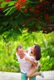 Glückliches Paar, das Spaß in blühendem Park hat Stockfoto