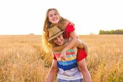 Glückliches Paar, das Spaß draußen auf Weizenfeld über Sonnenuntergang hat Lachende frohe Familie zusammen Getrennt auf Schwarzem stockbild