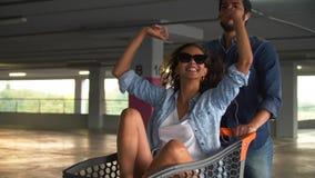 Glückliches Paar, das Spaß mit Einkaufswagen am Mall-Parken hat stock footage