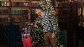 Glückliches Paar, das Spaß nahe dem Weihnachtsbaum hat stock video footage