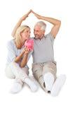 Glückliches Paar, das Sparschwein sitzt und schützt Stockfotografie