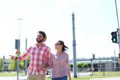 Glückliches Paar, das in Stadt gegen klaren Himmel geht Lizenzfreie Stockbilder