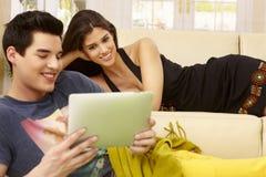 Glückliches Paar, das Tablette verwendet Stockfotografie