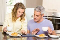 Glückliches Paar, das Tablette verwendet und frühstückt Stockbild
