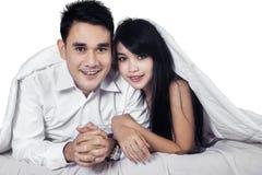 Glückliches Paar, das unter Decke sich versteckt Stockbild