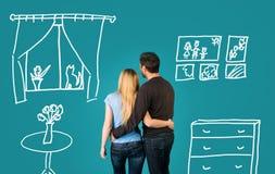 Glückliches Paar, das von ihrem neuen Haus träumt und auf blauem Hintergrund versorgt stockfotos