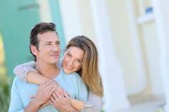Glückliches Paar, das vor Haus umfasst Lizenzfreie Stockfotos