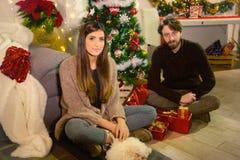 Glückliches Paar, das vor Weihnachtsbaum mit Geschenken lächelt stockbilder