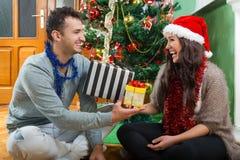 Glückliches Paar, das Weihnachtsgeschenke lacht und genießt stockfotografie