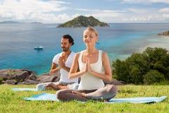 Glückliches Paar, das Yoga tut und draußen meditiert Lizenzfreies Stockfoto